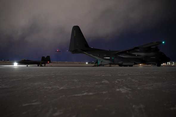Forward Area Refueling Point aircrew members with the 27th Special Operations Wing refuel an F-22 Raptor with the 3rd Wing from an MC-130J Commando II during Emerald Warrior at Joint Base Elmendorf-Richardson, Alaska, Jan. 30, 2020. This was considered the first-ever simulated Forward Area Refueling Point for F-22 Raptors in an extreme cold weather environment. Emerald Warrior 20-1 provides annual, realistic pre-deployment training encompassing multiple joint operating areas to prepare special operations forces, conventional force enablers, partner nations, and interagency elements to integrate with and execute full spectrum special operations in an arctic climate, sharpening U.S. forces' abilities to operate around the globe. (U.S. Air Force photo by Staff Sgt. Ridge Shan)