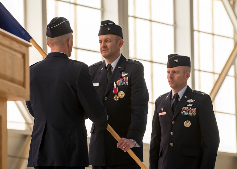 Brig. Gen. E. John Teichert, the outgoing 412th Test Wing Commander, relinquishes his command of the Wing by returning the unit's guidon to Maj. Gen. Christopher Azzano, Air Force Test Center Commander, during the Wing's Change of Command Ceremony at Edwards Air Force Base, California, Feb. 5. (Air Force photo by Giancarlo Casem)
