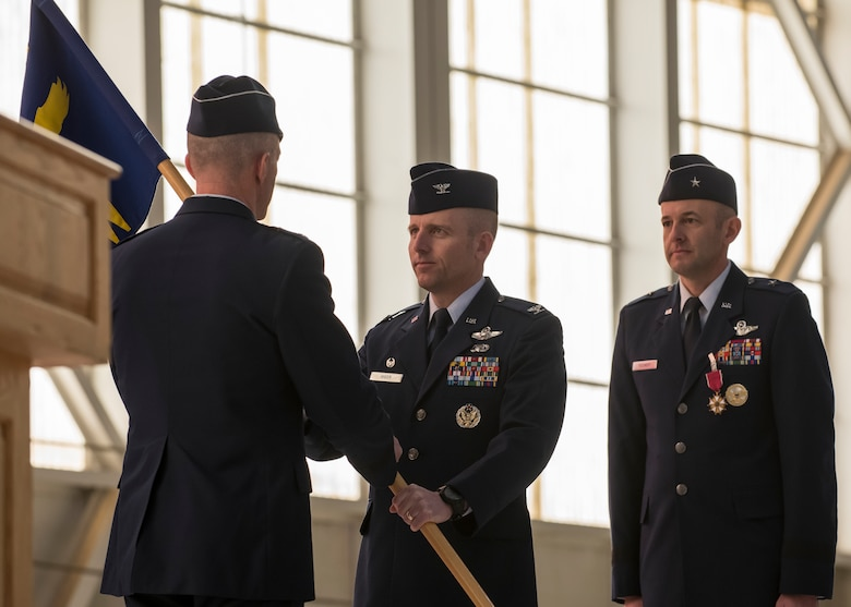 The 412th Test Wing's new commander, Col. Matthew Higer, assumes command of the Wing by receiving the unit guidon from Maj. Gen. Christopher Azzano, Air Force Test Center Commander, during the Wing's Change of Command Ceremony at Edwards Air Force Base, California, Feb. 5. (Air Force photo by Giancarlo Casem)