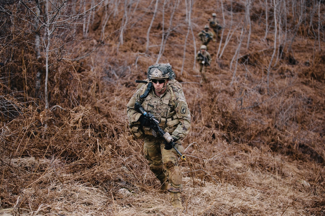A soldier in uniform carries a weapon in the woods while other soldiers trail behind.