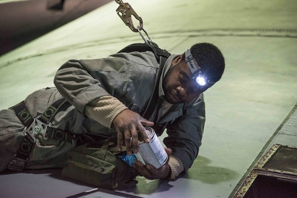 U.S. Air Force Master Sgt. Eugene Jackson of the 166th Maintenance Squadron fuel systems maintenance shop, Delaware Air National Guard, prepares to reseal a leaky fuel system access door on top of the right wing of a C-130H2 aircraft. Because fuel system maintainers have to work in high places, they are required to clip into a safety harness. (Courtesy Photo)