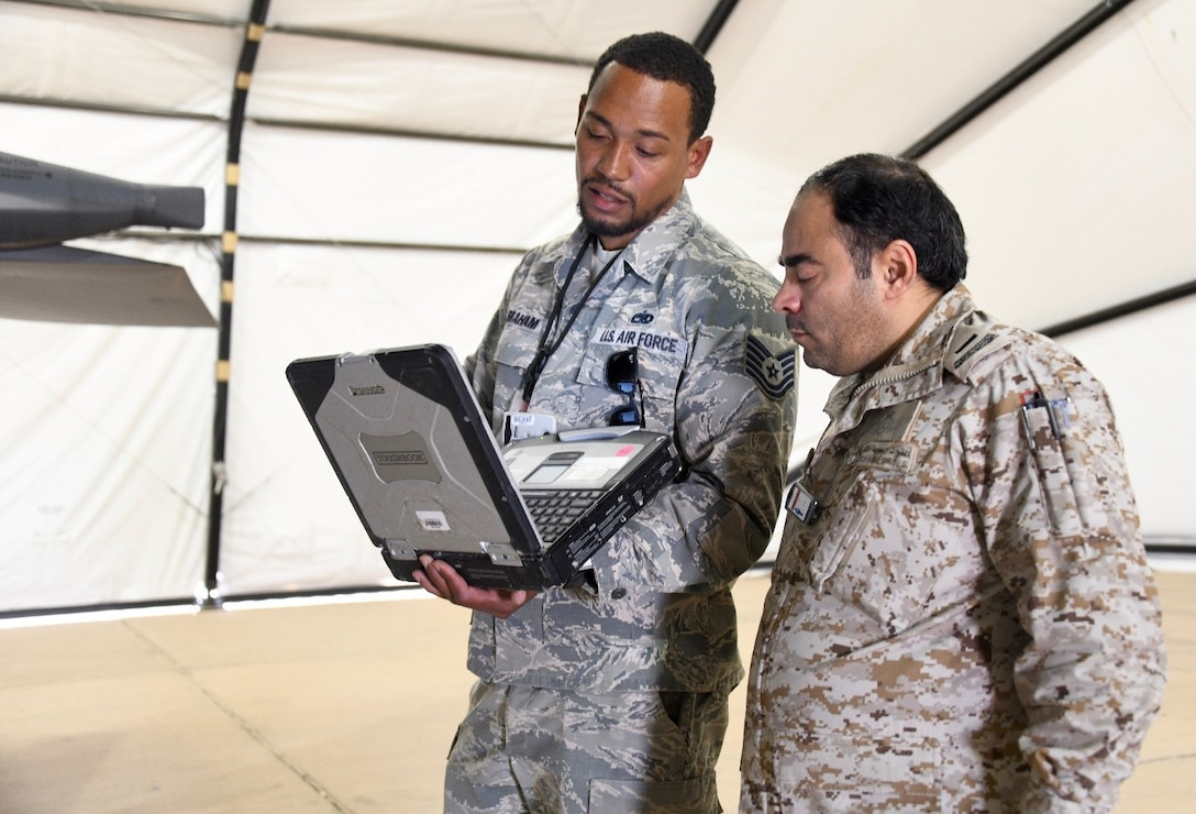 U.S. Air Force Tech. Sgt. Chris Graham (left), 378th Expeditionary Maintenance Squadron nondestructive inspection noncommissioned officer in charge, talks to Royal Saudi Air Force Chief Salman D. Al-Malki , PSAB head of aircraft maintenance inspections, about the processes of inspecting an F-15E Strike Eagle at Prince Sultan Air Base, Kingdom of Saudi Arabia, Feb. 4, 2020.