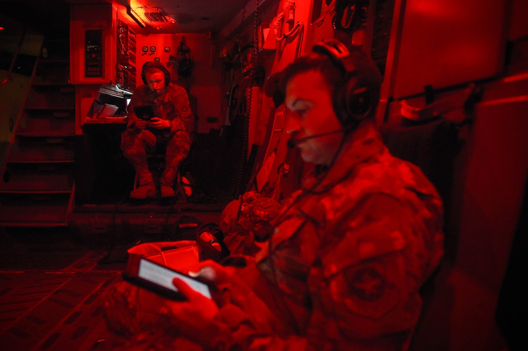 Airman 1st Class Kam Watt, left, and Master Sgt. Andrew Reilly, 4th Airlift Squadron loadmasters, review loadmaster Air Force Instructions (AFIs) aboard a C-17 Globemaster III in flight Dec. 18, 2019. Loadmasters don't have career development courses (CDCs) like some Air Force career fields, instead, they rely primarily on the guidelines laid out in the AFIs and flight manuals. (U.S. Air Force photo by Airman 1st Class Mikayla Heineck)