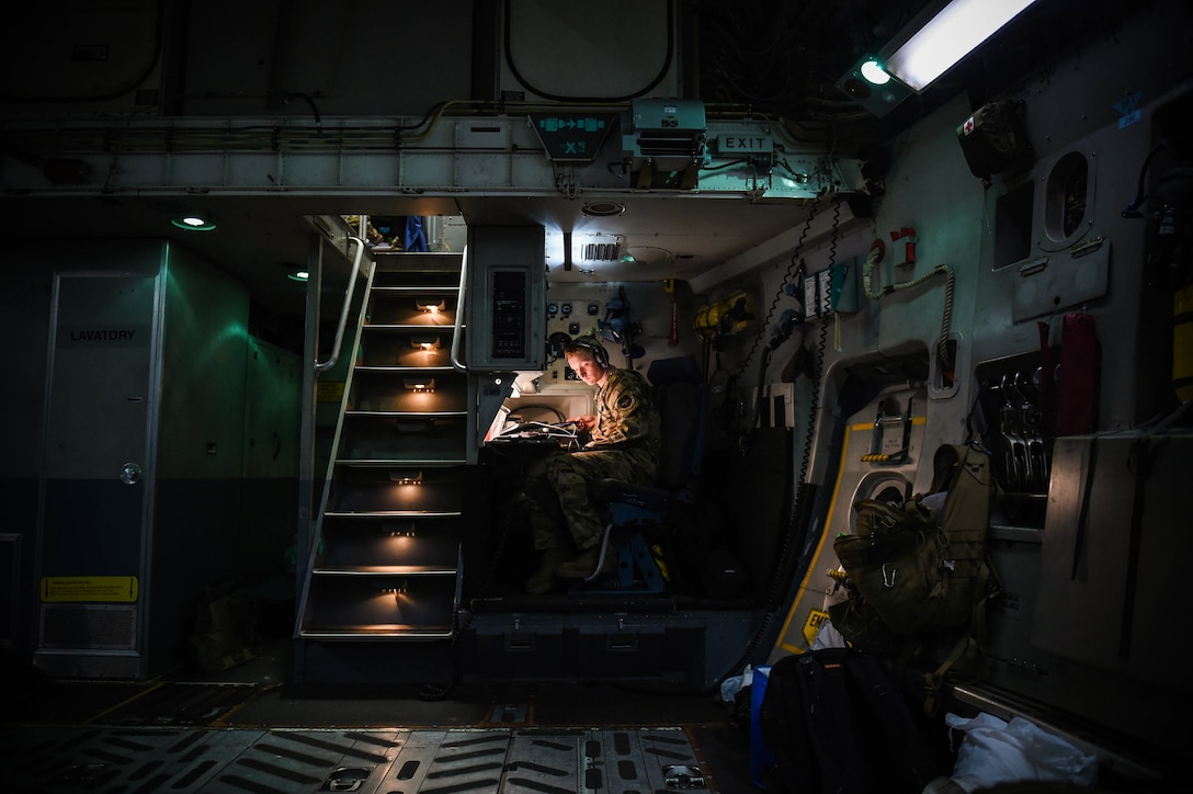 Airman 1st Class Kam Watt, 4th Airlift Squadron loadmaster, looks over a pre-flight checklist inside a C-17 Globemaster III before taking off from Iraq, Dec. 20, 2019. Loadmasters communicate with pilots upstairs in the flight deck via radio communications headsets. (U.S. Air Force photo by Airman 1st Class Mikayla Heineck)