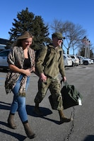 Photo of Senior Airman Brian Schreiner walking with girl friend at Hector International Airport, Fargo, N.D., upon his return from deployment Feb. 5, 2020.