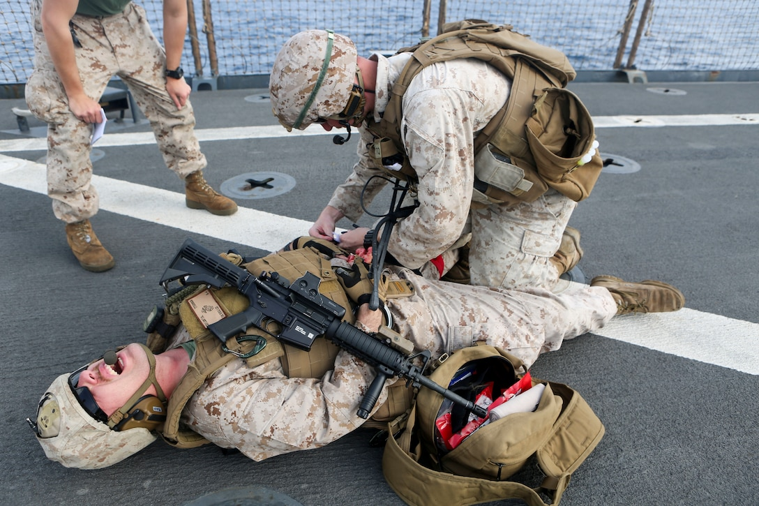 A Marine assigned to Combat Logistics Battalion 26, 26th Marine Expeditionary Unit, treats a simulated casualty as part of a combat life saver exercise aboard the amphibious dock landing ship USS Oak Hill.