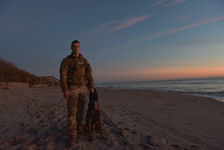 Staff Sgt. Kyle Pethtel, 45th Security Forces Squadron military working dog handler, poses for a photo with Pieter, his military working dog, at Patrick Air Force Base, Fla., Nov. 26, 2019. Pethtel and Pieter have been a MWD team since July 2019. (U.S. Air Force photo by Senior Airman Dalton Williams)