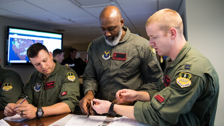 Karl Malone (center), NBA Hall of Famer, recieves a pre-flight brief prior to his flight with the 96th Bomb Squadron at Barksdale Air Force Base, La., Feb. 5, 2020. Malone spent time with Airmen, toured facilities and even took a ride in a B-52H Stratofortress. (U.S. Air Force photo by Airman 1st Class Jacob B. Wrightsman)