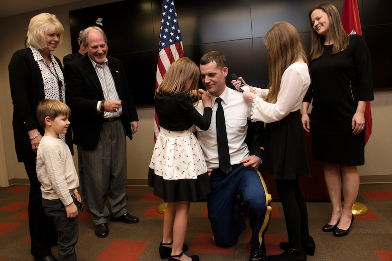 Maj. Justin Toole, U.S. Army Corps of Engineers Nashville District deputy commander, is supported by his family as his daughters Mya (Left) and Caroline put lieutenant colonel shoulder boards on his uniform during a promotion ceremony at the Nashville District Headquarters in Nashville, Tennessee, Feb. 6, 2020. From Left to Right supporting are his son Ben, mother Arlene, father Rick, and wife Katy. (USACE Photo by Lee Roberts)