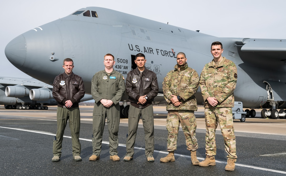 C-5M Super Galaxy 9th Airlift Squadron aircrew members pose for a photo Feb. 4, 2020, on Dover Air Force Base, Del. From the left are five of the 12 Reach 190 members: Capt. Geoffrey Howard, aircraft commander; Tech. Sgt. Alexander Barnes, flight engineer; Master Sgt. Joshua Cutrer, loadmaster; Staff Sgt. Teagan Young, 436th Aircraft Maintenance Squadron flying crew chief; and 1st Lt. Eli Parsch, pilot. (U.S. Air Force photo by Roland Balik)