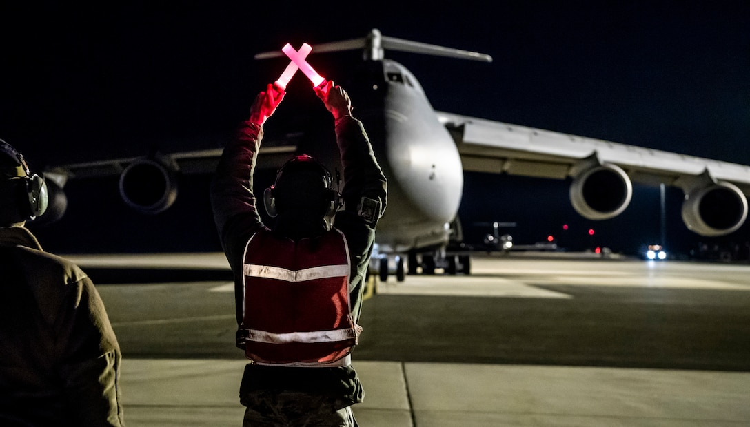 An aircraft maintainer from the 436th Aircraft Maintenance Squadron blocks in the C-5M Super Galaxy dubbed Reach 190 Jan. 28, 2020, on Dover Air Force Base, Del. The aircrew, consisting of 9th Airlift Squadron and 436th Aircraft Maintenance Squadron personnel, started on their mission Jan. 13, 2020, only to return to Dover 15 days later after encountering numerous challenges and an inflight medical emergency along the way. (U.S. Air Force photo by Senior Airman Christopher Quail)