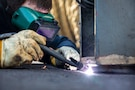 A sailor wears protective goggles while welding.
