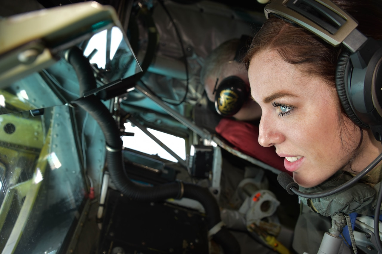An airman  wearing a headset looks out the window of an aircraft.