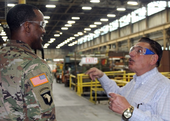 DLA Troop Support Commander Army Brig. Gen. Gavin Lawrence, left, smiles as SPS Technologies Sales Manager Joseph DiGiacomo, right, provides an overview of SPS' recapitalization of scrap material and how the industry works during a tour of the Jenkintown, Pennsylvania facility Feb. 5, 2020.