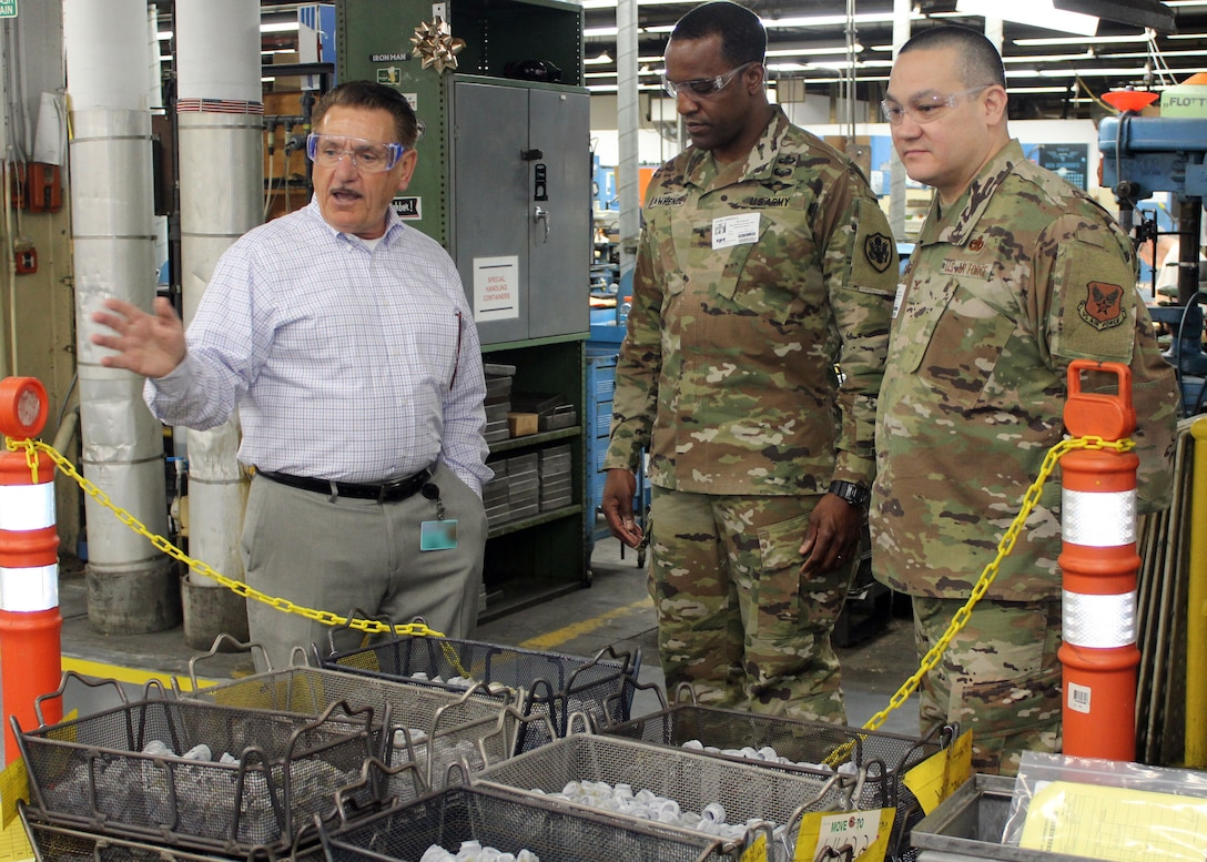 DLA Troop Support Commander Army Brig. Gen. Gavin Lawrence, center, and Industrial Hardware Director Air Force Col. Adrian Crowley, right, listen as SPS Technologies Sales Manager Joseph DiGiacomo explains the manufacturing process that goes into items at the Jenkintown, Pennsylvania facility Feb. 5, 2020.