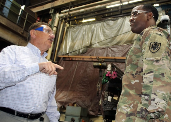 DLA Troop Support Commander Army Brig. Gen. Gavin Lawrence, right, listens as SPS Technologies Sales Manager Joseph DiGiacomo, left, explains how raw materials used in manufacturing are tracked all the way to the end product during a facility tour Feb. 5, 2020 in Jenkintown, Pennsylvania.