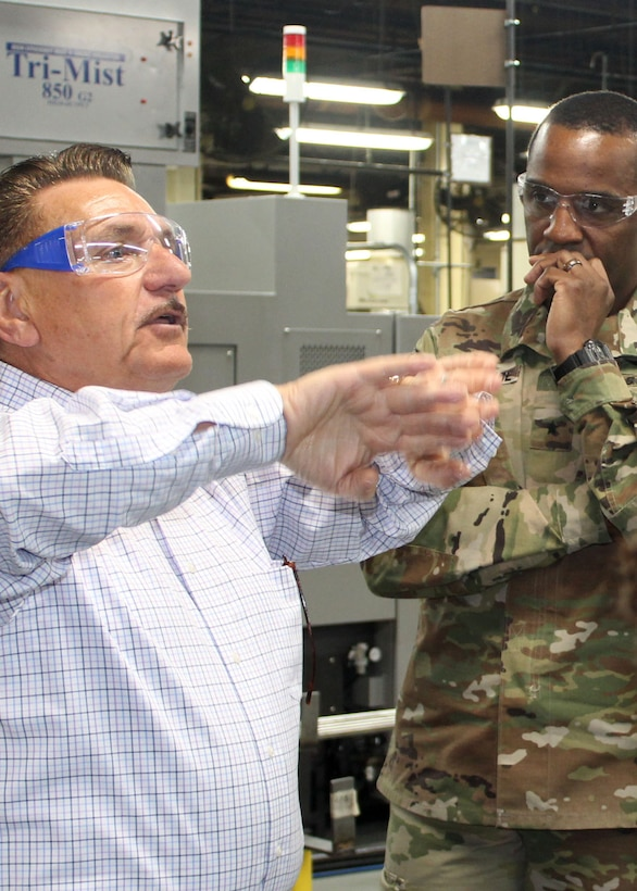 DLA Troop Support Commander Army Brig. Gen. Gavin Lawrence, right, listens as SPS Technologies Sales Manager Joseph DiGiacomo, left, describes a process SPS uses to strengthen the narrower parts of threaded hardware items during a tour of the Jenkintown, Pennsylvania facility Feb. 5, 2020.