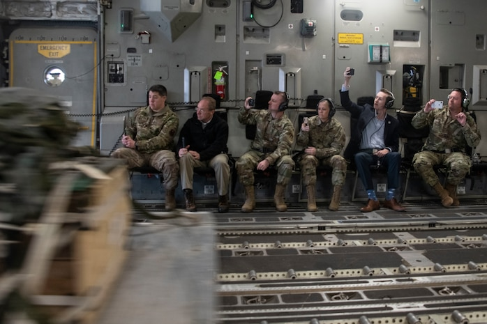 Members of the Oklahoma Commanders Summit watch as an air drop pallet slides out of a C-17 Globemaster III