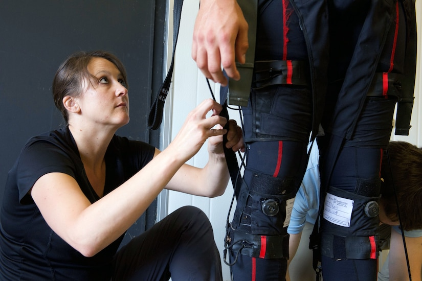 Dr. Courtney Webster makes adjustments to Warrior Web physical augmentation suit from Harvard's Wyss Institute in Boston, Massachusetts (Army Research Laboratory/David McNally)