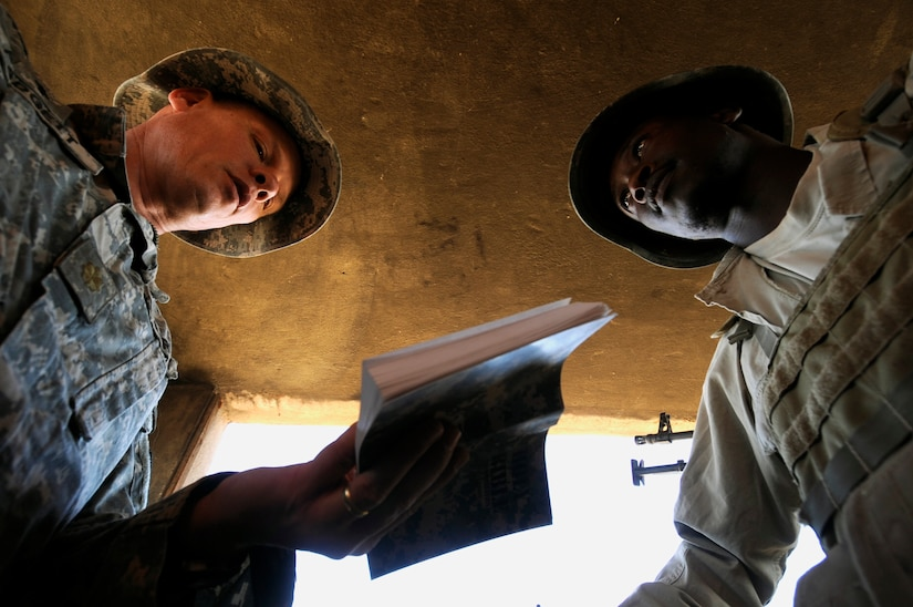 Chaplain with 2nd Battalion, 114th Strike Field Artillery Regiment, Mississippi National Guard, reads passage from Bible during visit with Ugandan security guards in security tower at Forward Operating Base, Marez, Mosul, Iraq, September 24, 2009 (U.S. Navy/Carmichael Yepez)
