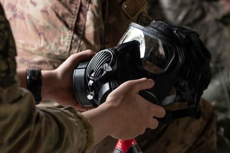 A photo of an Airman checking his gas mask during a chemical, biological, radiological, nuclear, and explosive defense training.