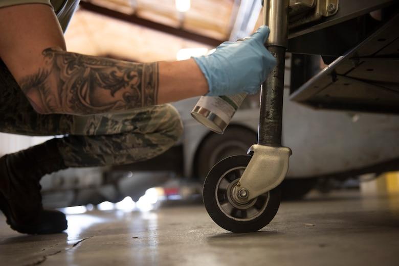 A photo on an Airman spraying a generator