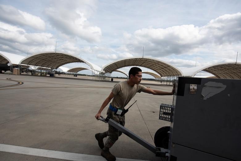 A photo of an Airman pushing a generator.