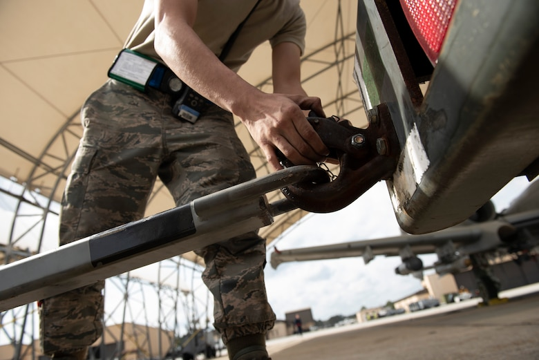 A photo of an Airman unhooking a generator from a truck