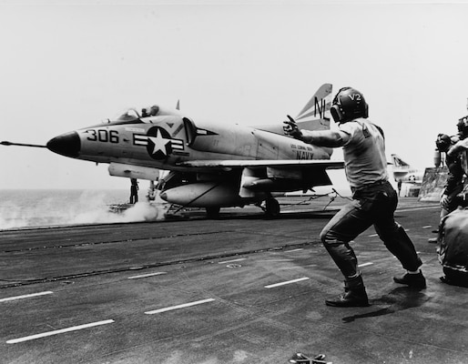 Catapult officer signals launch as A-4 Skyhawk starts down flight deck of USS Coral Sea during operations in South China Sea, March 24, 1965 (U.S. Navy/James F. Falk)