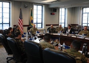 Military personnel sit and talk at a table.