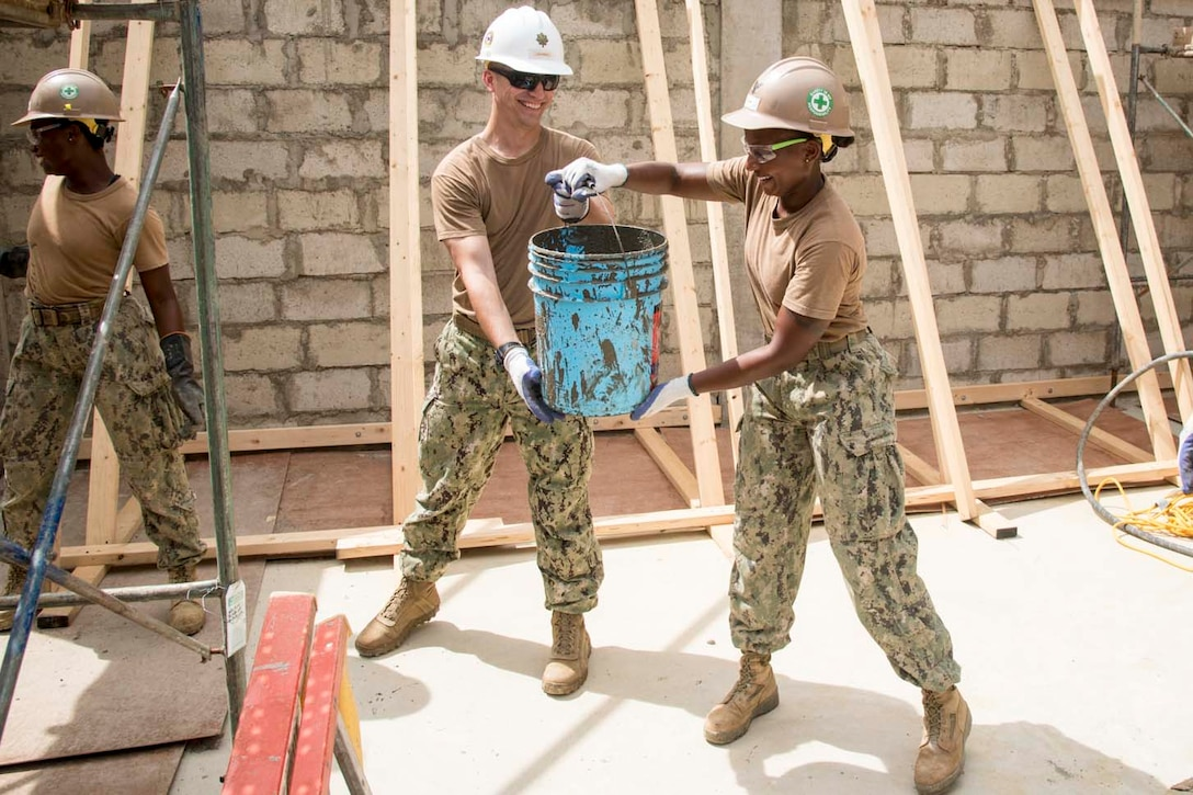 A sailor passes a bucket to another sailor.
