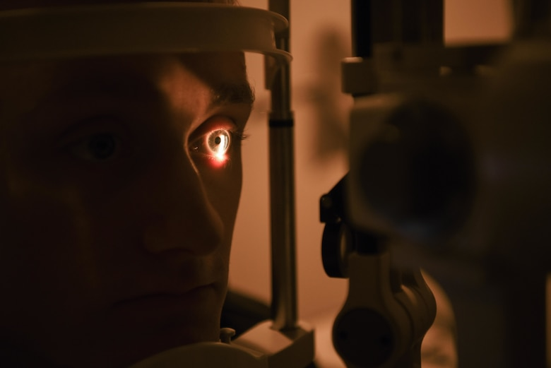 Senior Airman gets his eyes checked using a slit lamp