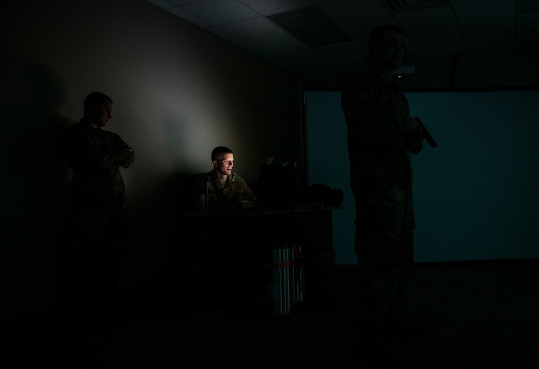 U.S. Air Force Staff Sgt. Michael McDowell, 325th Security Forces Squadron standards and evaluations evaluator (center), prepares a training scenario for Staff Sgt. Thomas Badders, 325th SFS noncommissioned officer in charge of confinement, at Tyndall Air Force Base, Florida, Feb. 5, 2020. Security Forces uses the Multiple Interactive Learning/Training Objectives Range to train for real-world situations. (U.S. Air Force photo by Senior Airman Stefan Alvarez)