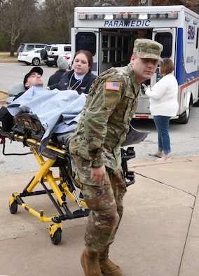 An EMSA EMT and a member of the Oklahoma Army National Guard bring Airman First Class James Lambert, 552nd Training Squadron, into a hospital at Metro Tech Health Careers Center during a mass casualty exercise Jan. 30. The joint effort event between Metro Tech, Tinker Air Force Base, the Army National Guard, Oklahoma City Fire and Police departments and EMSA saw between 300-400 participants which helped the students receive a more real-world experience to practice their knowledge and skills. (U.S. Air Force photo/Kelly White)