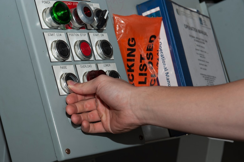 Photo of an Airman pressing a button on a control board