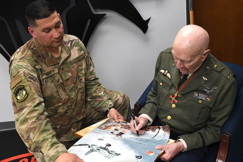 U.S. Air Force retired Col. Gail S. Halvorsen,  right, the Berlin Candy Bomber, autographs a photo for Master Sgt. Christopher Swartz, left, 821st Contingency Response Squadron aerial port flight chief, Jan. 31, 2020, Travis Air Force Base, California. As part of his visit, Halvorsen visited the 821st CRS where he spoke about the importance of being a part of the airlift team and told Airmen there was no greater service than to save the lives of others. (U.S. Air Force photo/ TSgt Liliana Moreno)