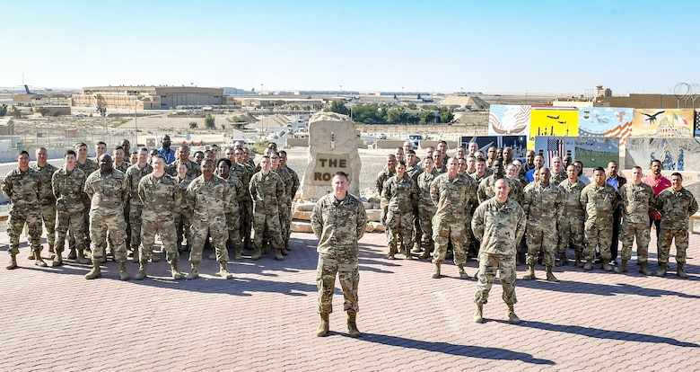 U.S. Air Force Senior Master Sgt. James Berg, current superintendent of the 386th Expeditionary Communications Squadron, 386th Expeditionary Wing, Ali Al Salem Air Base, Kuwait, pauses to stand with his squadron while serving overseas.