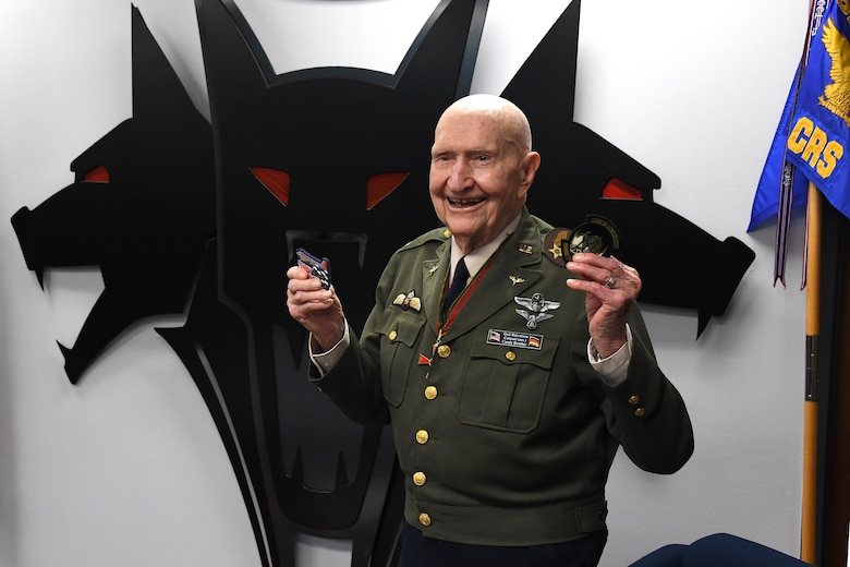 """U.S. Air Force retired Col. Gail S. Halvorsen, the Berlin Candy Bomber, smiles as he displays the patches given to him by  Airmen assigned to the 821st Contingency Response Squadron during his visit to Travis Air Force Base, California, Jan. 31, 2020. The 99-year old war hero shared his amazing story with the Airmen and as a tribute to his legacy, he was inducted into the squadron's """"Super Howl"""" hall of fame. The Super-Howl was initiated by the squadron as a way to recognize military veterans who visit their unit and have played an important role in the nation's history. The squadron displays this honor on a plaque at the unit where they add the name of the inductee next to the operation he or she served in. (U.S. Air Force photo/ TSgt Liliana Moreno)"""