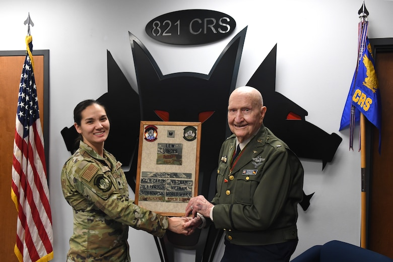 """U.S. Air Force Lt. Col. Christina Lee, 821st Contingency Response Squadron commander, and retired Col. Gail S. Halvorsen, hold a plaque which displays Halvorsen's name in recognition of his legacy as Berlin's Candy Bomber, Jan. 31, 2020, Travis Air Force Base, California. The 99-year old war hero shared his amazing story with the Airmen and as a tribute to his legacy, he was inducted into the squadron's """"Super Howl"""" hall of fame. The Super-Howl was initiated by the squadron as a way to recognize military veterans who visit their unit and have played an important role in the nation's history. The squadron displays this honor on a plaque at the unit where they add the name of the inductee next to the operation he or she served in. (U.S. Air Force photo/ TSgt Liliana Moreno)"""