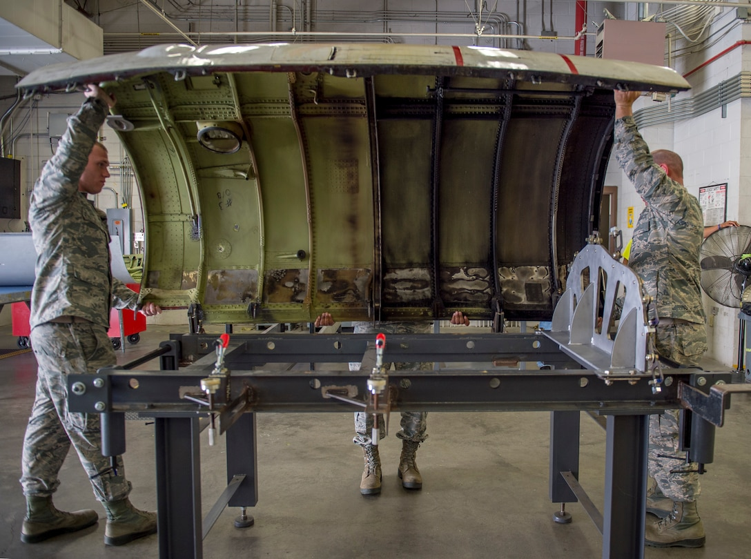 Sheet metal technicians with the Georgia Air National Guard's 116th Air Control Wing and the 461st Air Control Wing secure an engine aircraft cover on a cowling fixture table at Robins Air Force Base, Georgia, April 3, 2019.