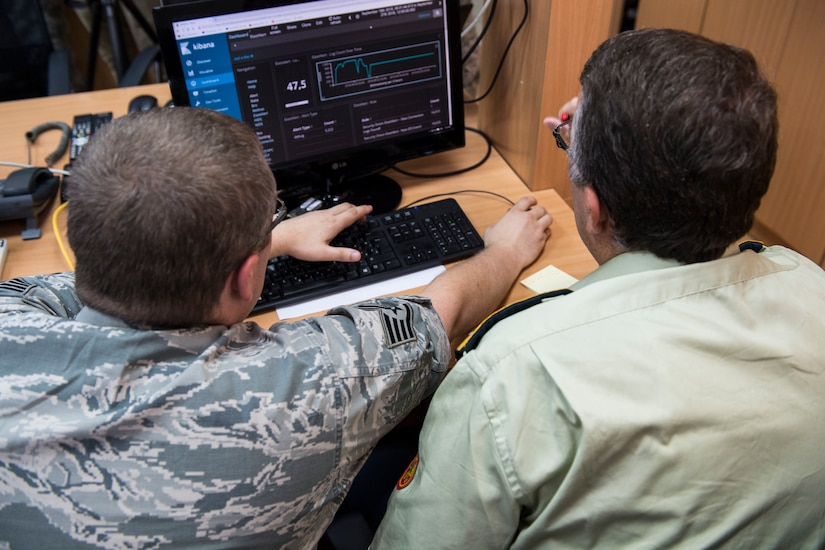 A U.S. airman and a service member from Montenegro work together at a computer monitor.