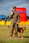 U.S. Marine Corps Cpl. Isaac Cutshaw, a marine working dog (MWD) handler with 3rd Law Enforcement Battalion, speaks to an audience about the capabilities of MWD Gage, a specialized search dog, during Hansen Fest, Camp Hansen, Okinawa, Japan, Feb. 8, 2020. The festival was held to bring members of the local and U.S. military communities together to build relationships through festivities and live performances. (U.S. Marine Corps photo by Lance Cpl. Zachary Larsen)