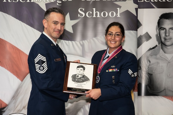 U.S. Air Force Chief Master Sgt. Jason Redfern, 52nd Logistics Readiness Squadron chief enlisted manager, left, presents the John L. Levitow award to Senior Airman Deema Alnaama, 52nd Aircraft Maintenance Squadron weapons load crew member, during the Pitsenbarger Airman Leadership School class 20-B graduation at Spangdahlem Air Base, Germany, Feb. 7, 2020. The award is given to the ALS graduate who demonstrates the most professional leadership and academic performance. (U.S. Air Force photo by Airman 1st Class Valerie Seelye)