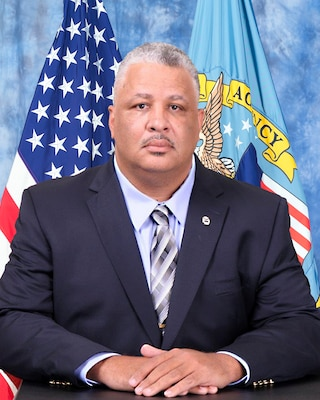 official photo with blue background and American and DLA flags behind man in suit