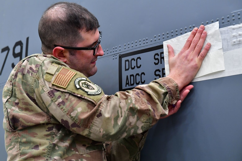 Senior Airman Kahlin Dawson, 19th Aircraft Maintenance Squadron crew chief, unveils his name on his assigned aircraft as part of the Dedicated Crew Chief program.