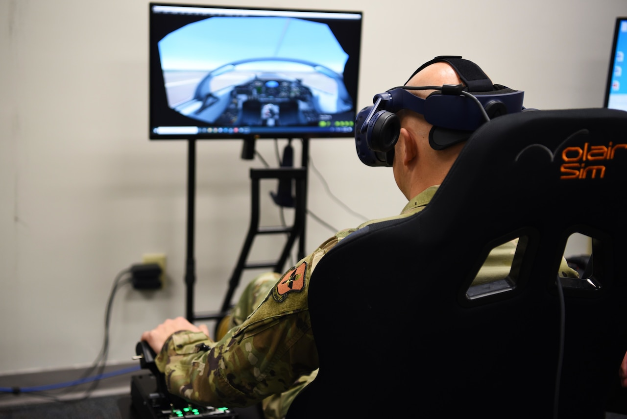 An airman sitting in a large chair and wearing virtual reality goggles faces a screen with an airplane cockpit on it.