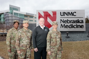 (From left) Maj. Kisha Wood, The Center for the Sustainment of Trauma Readiness Skills Omaha deputy director, Tech. Sgt. Victor Kipping, public health non-commissioned officer in charge, Bob Valentine, C-STARS Omaha administrator, and Lt. Col. Elizabeth Schnaubelt, C-STARS Omaha director, pose for a photo in front of The University of Nebraska Medical Center, Omaha, Nebraska, Jan. 3, 2020. The U.S. Air Force's C-STARS Omaha program, which was established in 2018, partners with the University of Nebraska Medical Center, focusing on advancing the training of medical Airmen in infectious diseases they might see during deployment. (Courtesy photo)