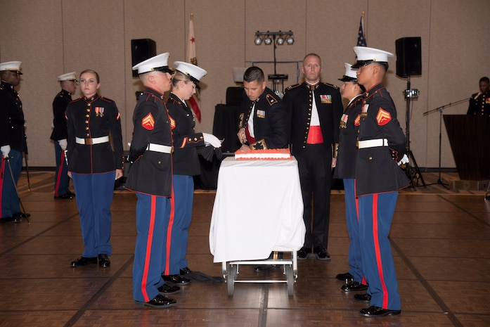 Commanding officer of CLB-5 cuts birthday cake during Marine Corps' birthday ball ceremony.