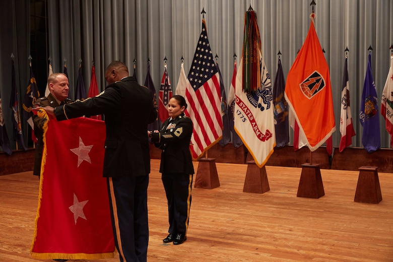 U.S. Army Reserve Maj. Gen. John Phillips (left) and Command Sgt. Maj. Edward Simpson unfurl his 2-star flag during his promotion ceremony held in Alexander Hall, Fort Gordon, Ga. Feb. 9, 2020.