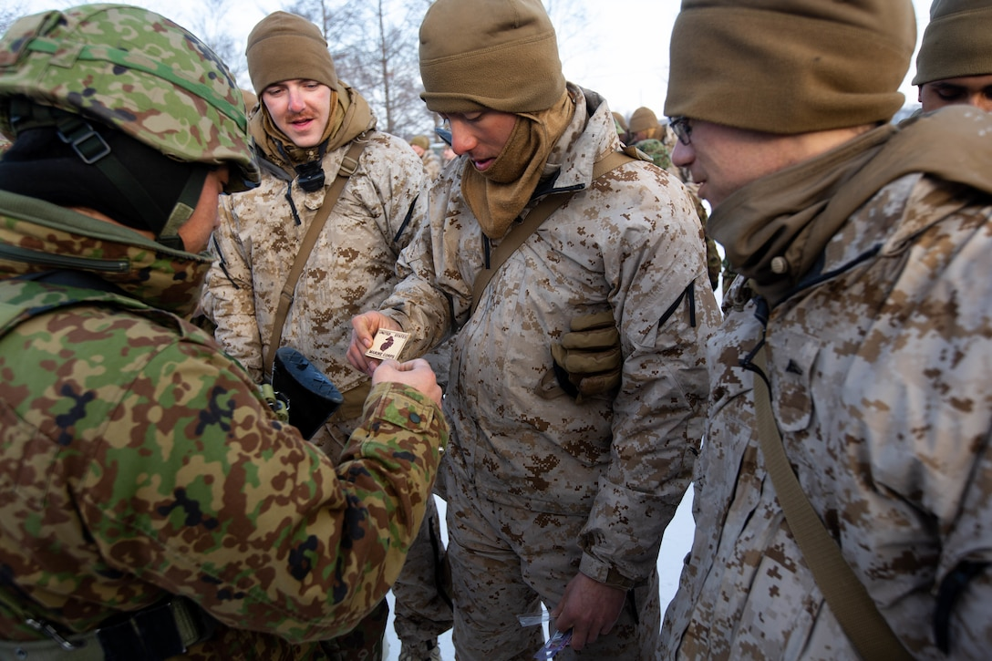 U.S. Marines with 1st Battalion, 25th Marine Regiment, and members of the 5th Brigade, Japan Ground Self-Defense Force, exchange gifts after the ceremony concluding the end of exercise Northern Viper on Yausubetsu Training Area, Hokkaido, Japan, Feb. 8.